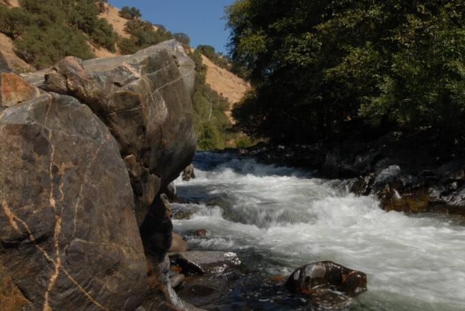 ModernJeeper Del Albright photo of giant rock alongside river rapids.