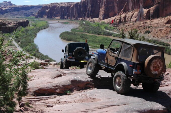 Moab Rim Trail, Utah, with Jeeps overlooking Colorado River by Del Albright.